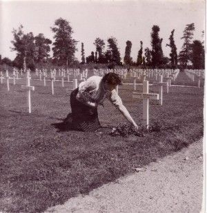 """Madame Simone Renaud tended graves of American GIs killed during World War II. Here, she places flowers on the grave of Brig. Gen. Theodore Roosevelt Jr. A similar photograph ran in Life magazine in 1944."""