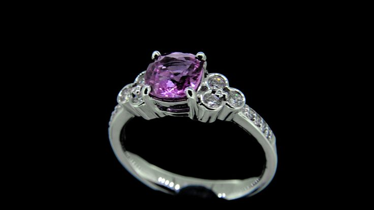 'Davina' -- Candy Pink Cushion Cut Sapphire Engagement Ring set with Shoulder Bezel Set Diamonds with Accent set Band in 18ct White Gold. Sapphire Wt. 1.45ct; Diamond Wt. 0.16ct - G/VS.