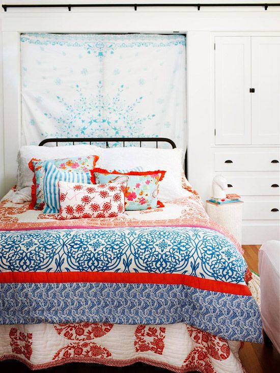 A pretty patterned sheet, tablecloth, or fabric hung behind the bed makes an instant, laid-back wall accent | BHG