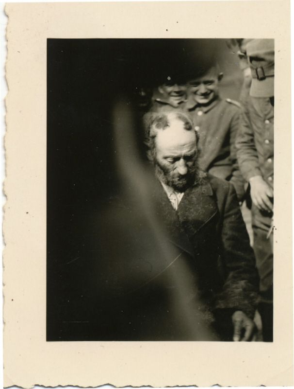 German soldiers delight in the shaving of a swastika onto the head of a religious Jewish man. Nazi-occupied Poland early 1940s. [606800]