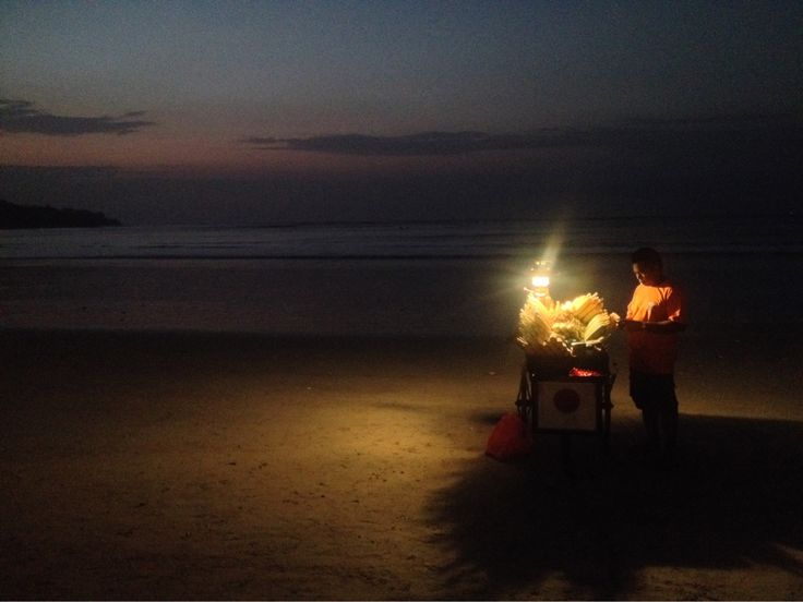 Corn seller at Jimbaran Beach, Bali, October 2013. The fishing village and coastal resort's fine, white sands, calm waters and stunning sunset view attracts crowds of people to the beach every evening where mobile stalls as pictured serve tourists and locals right on the shoreline with unmistakable Bali hospitality.