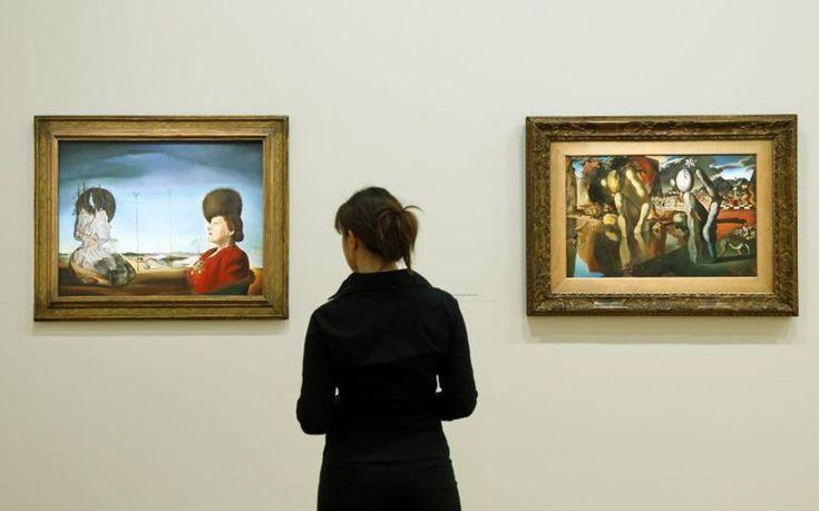 visitor looks at at paintings 'Portrait de madame Isabelle Styler-Tas (Melancolie) 1945' (Portrait of Mrs. Isabel Styler-Tas - Melancholy) (L) and Metamorphose de Narcisse 1937 (Metamorphosis of Narcissus).