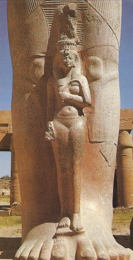 Dimunitive figure of a graceful queen Nefertari standing be-tween the legs of the colossal granite statue of Ramses II in the 1st courtyard of the temple at Karnak