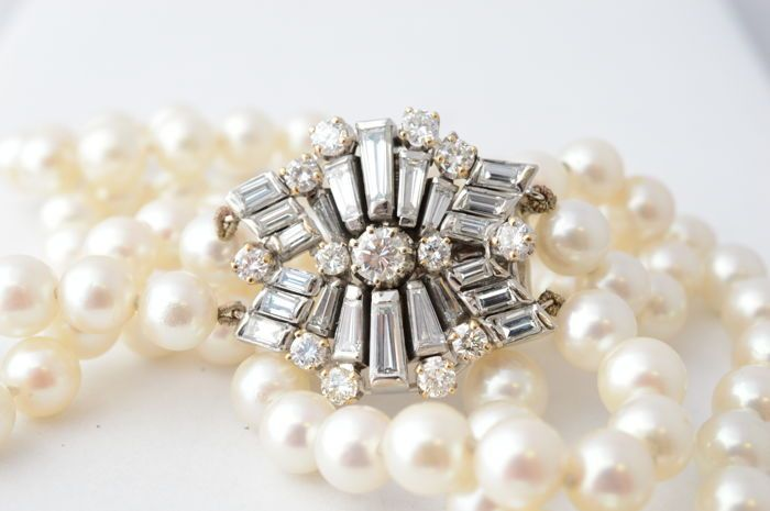 Diamanten 7 mm parel collier met grote sluiting bezaaid met diamanten - Lengte: Ca. 37 cm  Chique akoya parelketting met een prachtig grote witgouden bloem sluiting van platina. De schitterende sluiting is bezet met briljant diamanten en baguette diamanten. Ook is de ketting voorzien van een dubbele sluiting. Zoveel diamant in een parel sluiting is heel bijzonder en een zeer uniek schitterend object.Diamant (13 stuks)Slijpvorm: Briljant Gewicht: Ca. 2.00 ct. Kleur: RiverZuiverheid…
