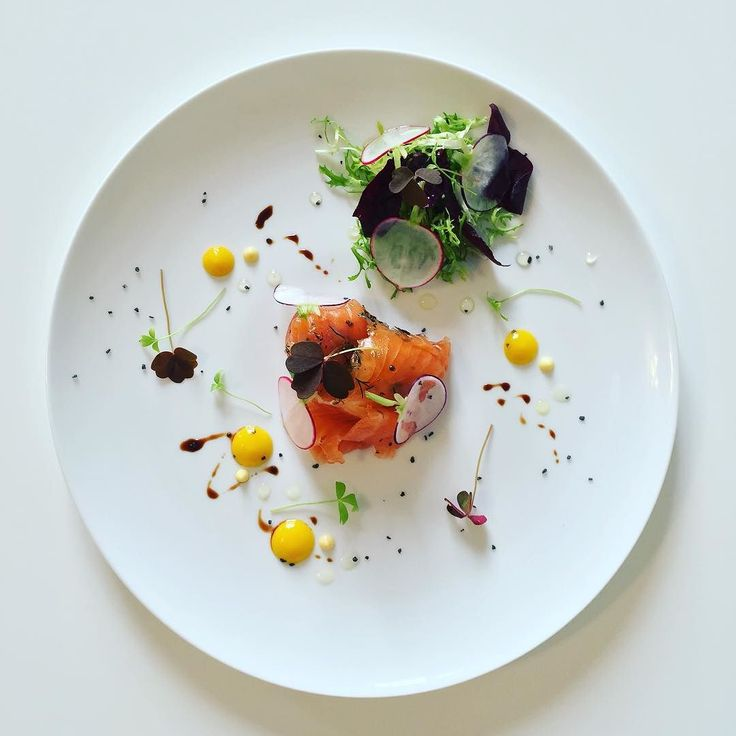 Smoked salmon served with small salad, baby pickled radishes and some kind of sauce.
