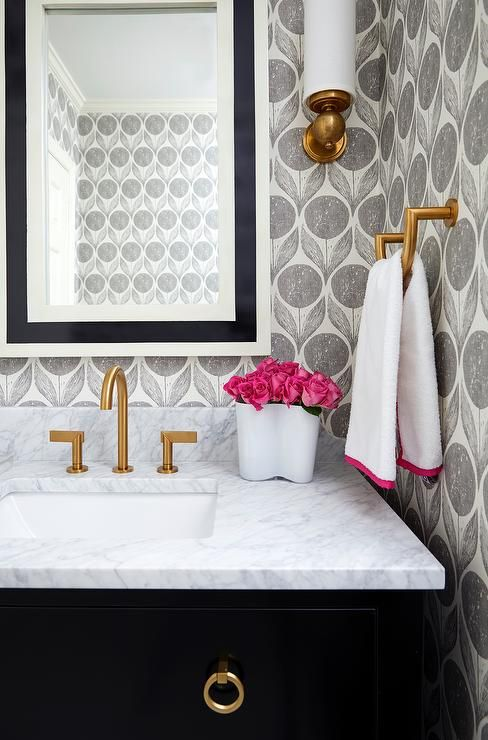 A black and white beveled mirror illuminated by an antique brass uplight sconce lines an ivory and gray floral print wallapper stands over a black sink vanity adorned with brass ring pulls topped with white quartz fitted with a white porcelain sink and brushed gold faucet.