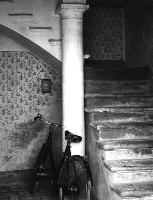 Paul Strand, Luzzara, Italy, ​1953. This photo uses a great use of contrast by utilizing the bright white post to draw attention toward the bike leaning against it, then up the darkening stair case.
