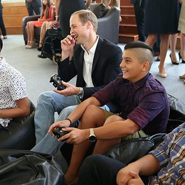 Three boys were sitting on big bean bag chairs playing a video game console. They made space for Prince William to sit with them and handed him a controller.