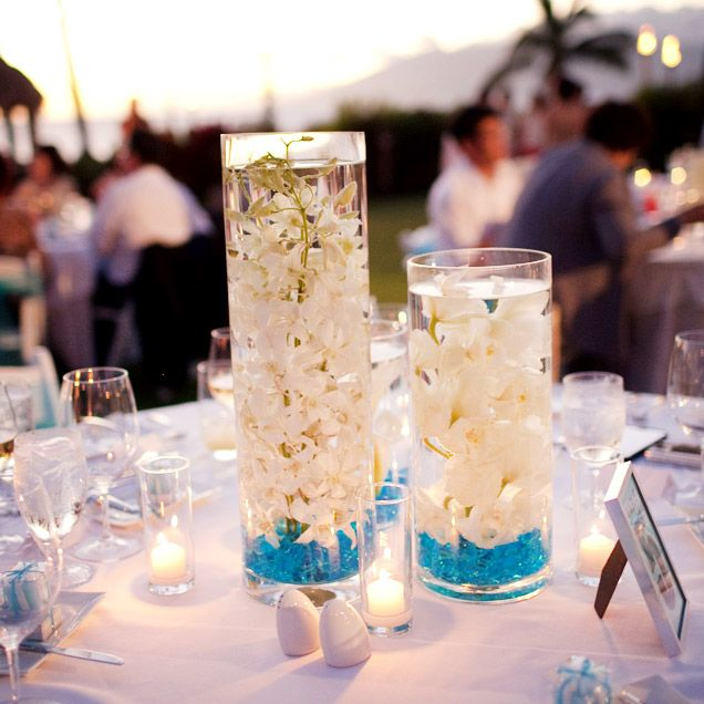 Centrepieces filled with turquoise rocks and floating white orchids brought a pop of tropical colour to @Mandy Dewey Seasons Resort Maui tablescapes.