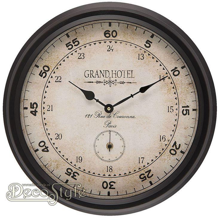 Wandklok Grand Hotel  Metalen wandklok met de tekst: Grand Hotel. Voor de wijzers zit een glasplaat. Deze klok heeft een aparte secondenwijzer Met Quartz uurwerk. Werkt op 2 penlight batterijen. Een sieraad voor in uw huis. Kleur: Bruin Materiaal: Metaal / Glas Vervaardigd door: Clayre & Eef Afmetingen: Hoogte: 42 cm Breedte: 42 cm Diepte: 8 cm