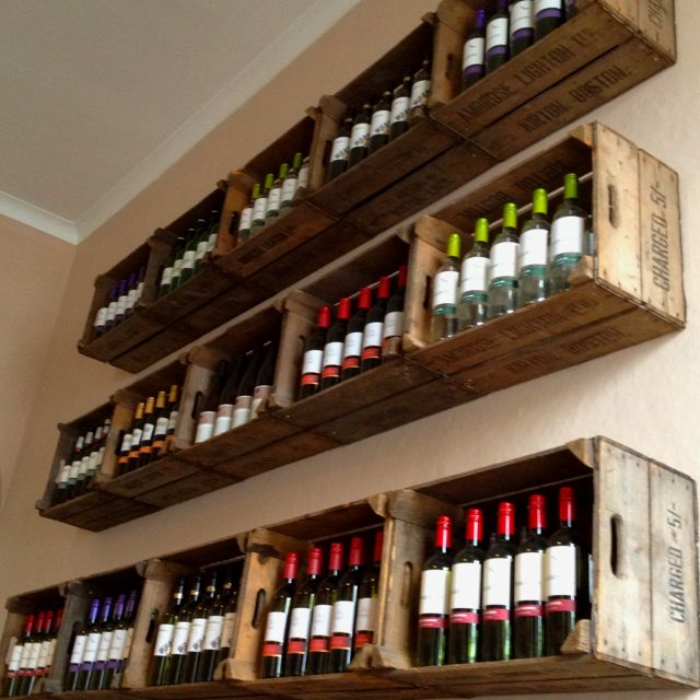 Vintage crates as shelves, One for wine and one for wine glasses in dining room.