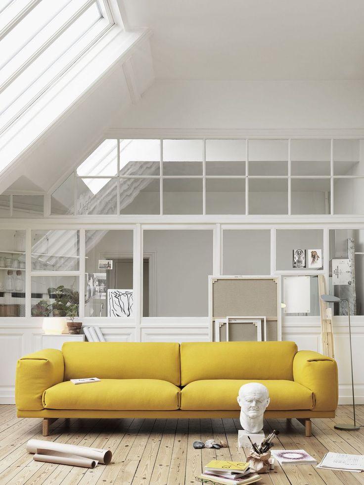 Un canapé design tissu jaune moutarde dans un salon blanc esprit atelier avec verrières