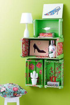 Estante de caixote pintada de verde e com as laterais revestidas com tecido.