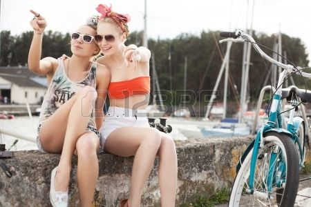 Holiday at the seaside Two beautiful women on a pier near yachts Outdoor lifestyle Stock Photo