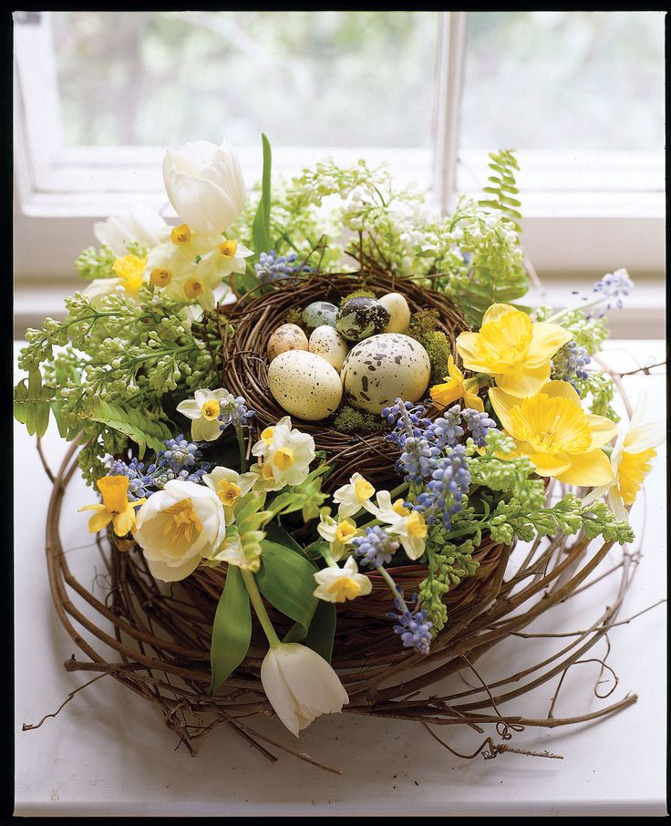 Flowers and eggs (real and artificial) rest in a bird's nest filled with wet florist's foam. Complete Instructions: Wreath of flowers with egg nest: Fill a 10-inch-round low basket with aluminum foil, then place florist's foam on top. Loosely loop grapevine (available at crafts stores) around the perimeter of the basket. Place a bird's nest (also available at crafts stores) in the center of the basket. Add artificial birds' eggs to the nest. Finish by arranging tulips, daffodils, grape…