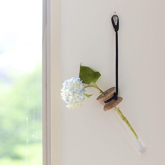 洗練された佇まいで印象的な空間を作り出す花器。ガラスと木の組み合わせが魅力の『eNproduct/エンプロダクト』の一輪挿しをご紹介します。一輪花をさすと、シックではかなげな空間の演出ができる花器です。四季折々の草花を愛でる楽しみを、暮らしに取り入れてみませんか?シックなシーンを作る一輪挿し。試験管のようなガラスの花器は、直径1.6cm、長さ16cmと小ぶりなため、花一輪が上品にいけられるサイズです。道ばたに咲いているような素朴な花が似合うような気がしませんか?身近なお花を試したり、気分に合うお花を探す時
