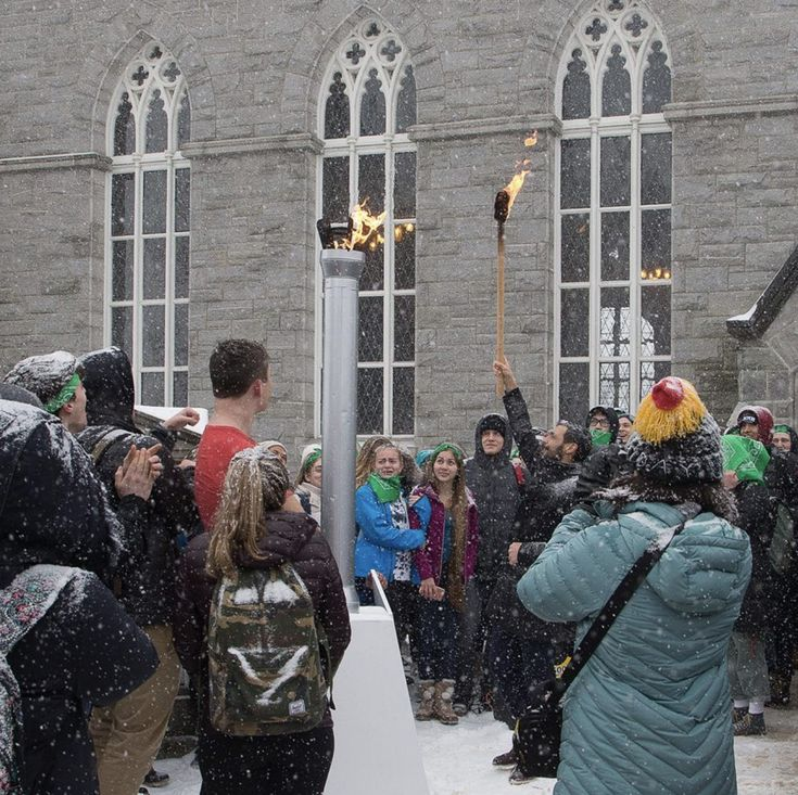 Torch bearer (and NMH teacher) Grant Gonzalez lights the Olympic flame outside Memorial Chapel on an appropriately wintry day. While athletes compete in the Korean Olympic games, NMH is staging its own contests. Events include water polo, bubble soccer, a trivia contest, and a secret-egg hunt. Glenn Minshall photo