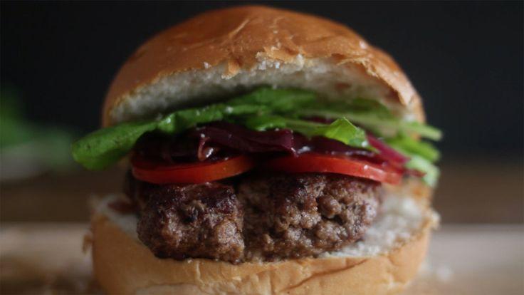 Receita com instruções em vídeo: Hambúrguer já é uma delícia e esse com recheio de gorgonzola fica melhor ainda! Ingredientes: 2 colheres de sopa de manteiga, 2 cebolas roxas, 2 colheres de sopa de açúcar, 2 colheres de sopa de balsâmico, Sal, 400g de carne moída, Pimenta preta, 100g de queijo gorgonzola, 4 pães de hambúrguer, Rodelas de tomate, Folhas de rúcula