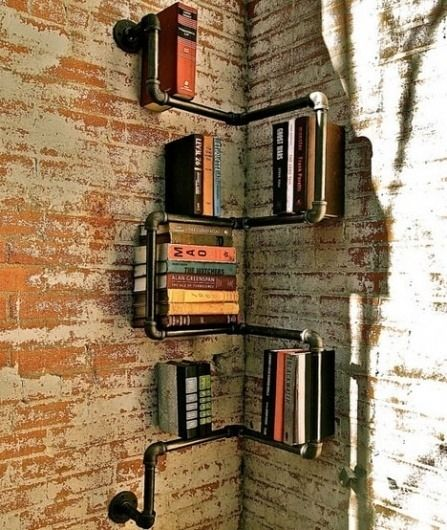 A bookshelf make of pipes add extra character yet fit right in with exposed brick walls. (via eyrequotes)