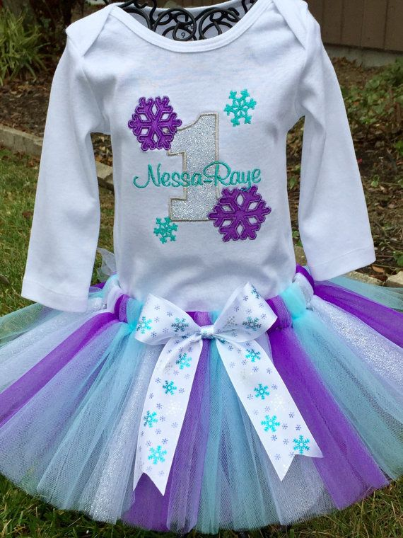 This adorable tutu set is perfect for the winter birthday princess  Tutu is made from yards of soft nylon tulle in shades of purple, aqua, white and silver and finished with snowflake bow. Your little princess will look pretty as a present.  Top is embroidered with the birthday number and finished with beautiful sparkling applique snowflakes. Set can be made to fit newborn up to 5 years old.  Approximate tutu measurements: Newborn - 3 months 15 waist 6 length 3 months - 6 months 16 waist 7…