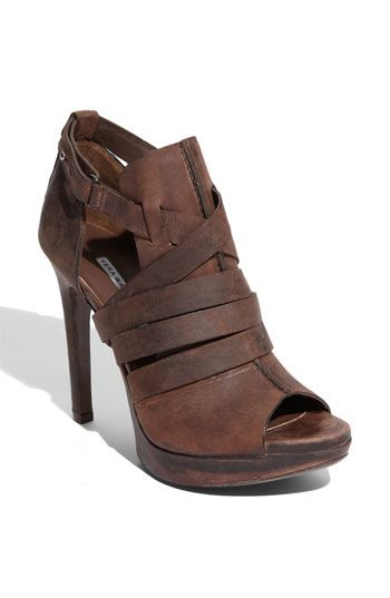 Crossing straps wrap the front of a distressed-leather bootie fashioned with a peep toe and cutout sides. A wrapped stiletto heel and platform provide sky-high elevation., $425.00