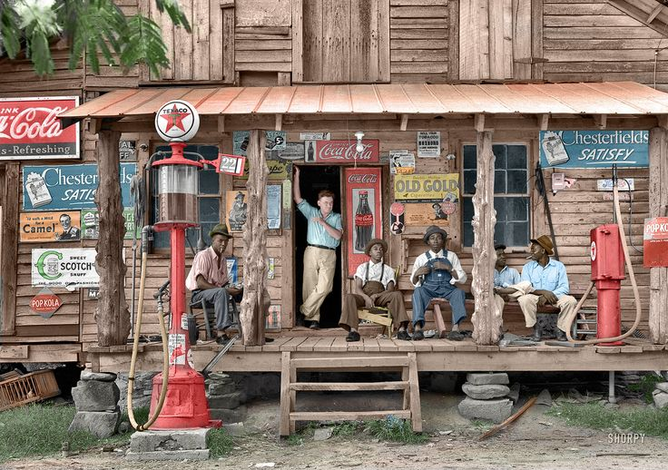 """(colorized) July 1939. Gordonton, North Carolina. """"Country store on dirt road. Sunday afternoon. Note kerosene pump on the right and the gasoline pump on the left. Rough, unfinished timber posts have been used as supports for porch roof. Negro men sitting on the porch. Brother of store owner stands in doorway."""" 4x5 negative by Dorothea Lange."""