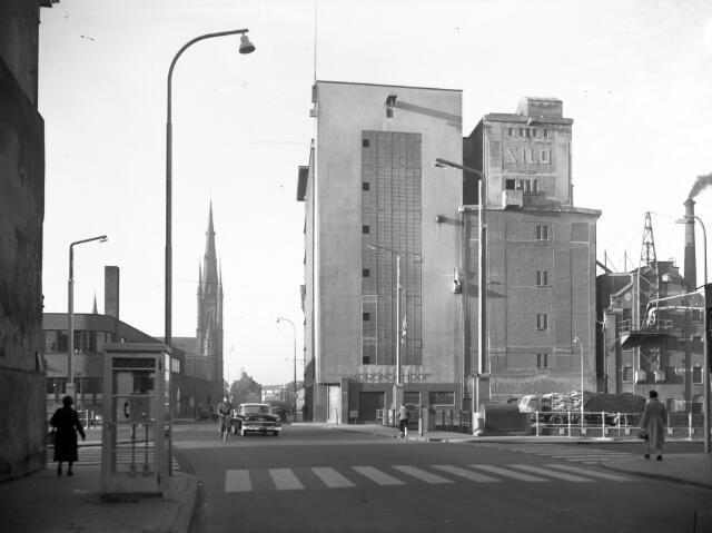 1955-1956. Gezicht op de silo's van de meelfabriek De Korenschoof (Kaatstraat) te Utrecht, vanaf de Adelaarstraat. Op de voorgrond de Stenenbrug over de Vecht en links een telefooncel. Op de achtergrond de toren van de St.-Monicakerk (Herenweg 99).