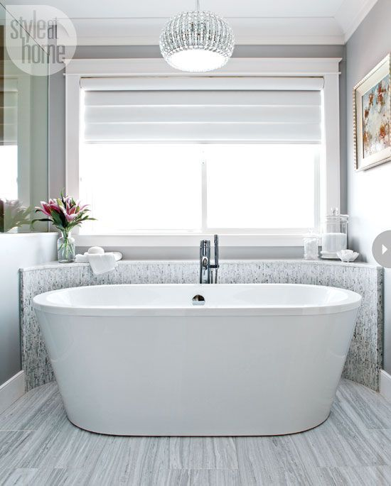 Modern glamour Elegance and glamour run high in this master bath thanks to the stunning Siberian White marble, cool colour palette, and sparkling decor accents like the chandelier and vanity mirror.