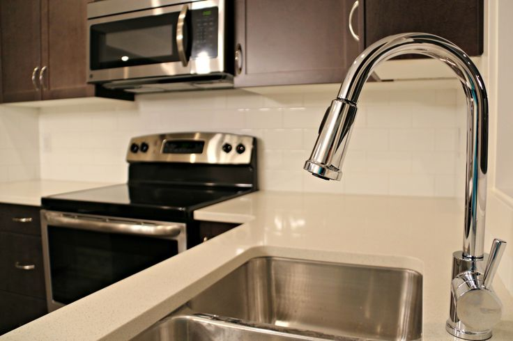 Stainless Steel appliances and white granite counter top.