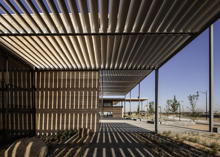 Wooden louvred sunscreens project from the rammed earth and glass walls of this Melbourne library.