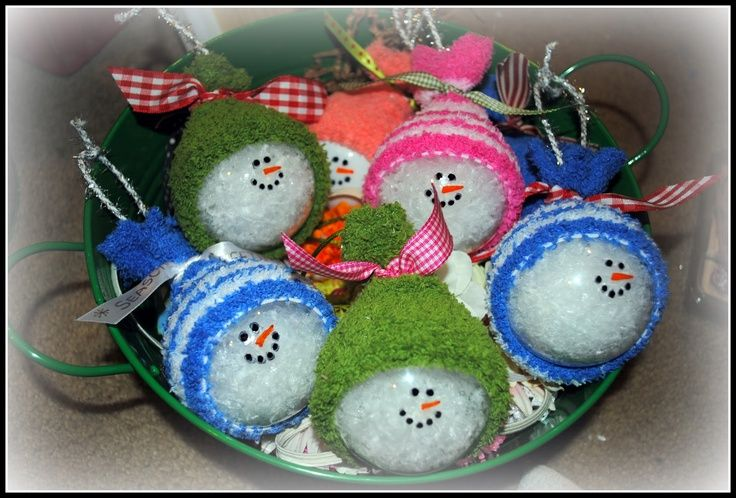 Snowmen Ornaments. Fill clear ornaments with fake snow, paint a cute face and top with a baby sock. How easy and super cute.