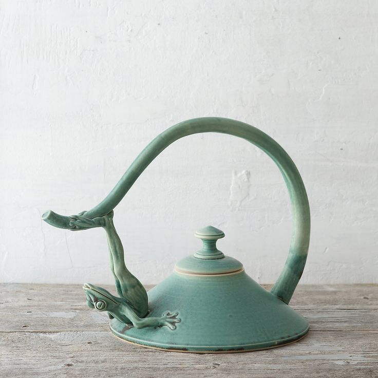 """An ornately sculpted frog supports the handle of this elegant teapot, each one hand-crafted by Utah artist Johnny Hughes and finished with a serene, blue-green glaze.- Glazed ceramic- Handmade in the USA12.5""""H, 11"""" diameter"""