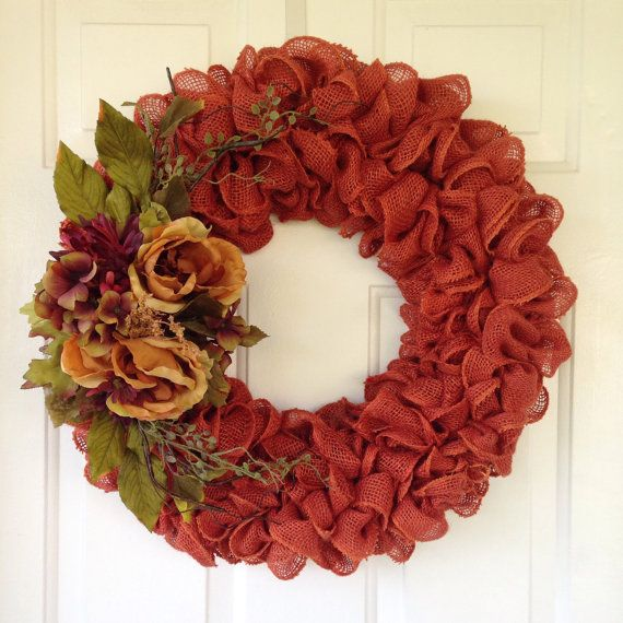 Rustic burnt orange burlap wreath accented with flowers and greenery