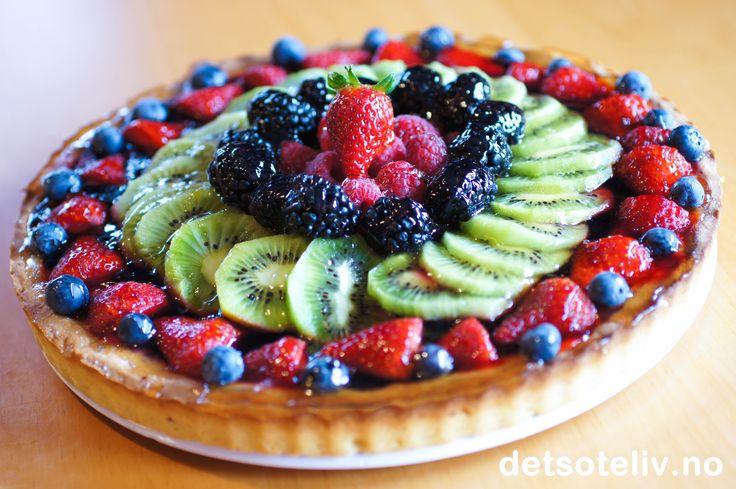 """Dette er en fransk frukt- og bærterte som virkelig smaker fruktig! I tillegg til den vakre toppingen, er terten fylt med blåbærfyll. Jeg har her brukt friske bær og kiwi på toppen av kaken, men en """"Tarte aux fruits"""" kan varieres og pyntes med den frukten og bærene du liker best. Smeltet eplegelé gir god smak og gjør overflaten blank og vakker."""