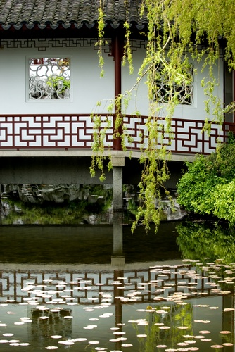 Repetition and balance in the mirrored water reflection of the railings and pillars