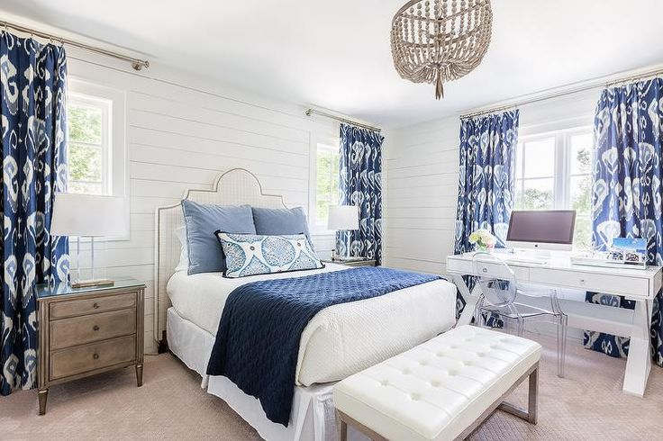 White and blue bedroom boasts shiplap walls lined with a white grid nailhead headboard on bed dressed in white and blue bedding flanked by gray French nightstands and glass lamps placed under windows dressed in blue ikat curtains, Bansuri Iris Fabric.