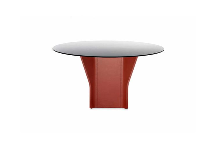 """ARGOR 140, design Kensaku Oshiro. The table, with its central base entirely covered in leather, recalls a piece of paper shaped to create an origami whose extremities seem """"pinched"""" and folded to achieve a three-dimensional contour. The glass surface, available in round or oval versions, is painted white, black or tortoise on the back and …"""