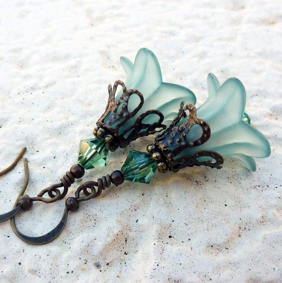 A lovely pair of teal and swarovski crystal flower earrings.  The lucite flowers are 16mm lily flowers from which dangles swarovski crystals. Antique brass filigree encases the flowers and on top of this is a larger swarovski crystal. Two little swarovski's dangle from beneath.  The earrings measure 3.5cm from the base of the hooks.