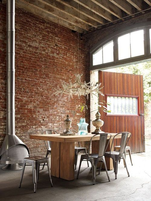 Rustic open dining room. Love the exposed brick and chimney!