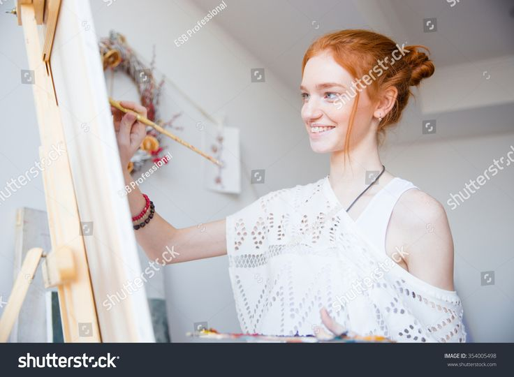 Smiling attractive young woman painter with red hair painting on canvas in artist workshop