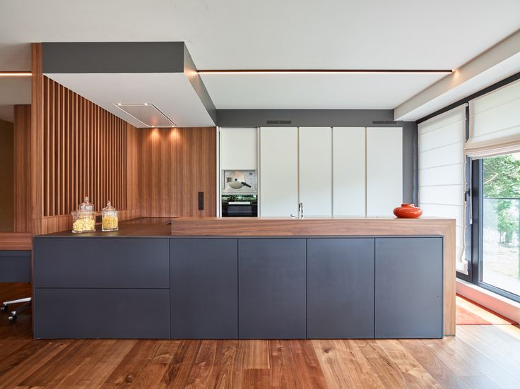 This SieMatic kitchen extends into an office area, with a modern mix of black…