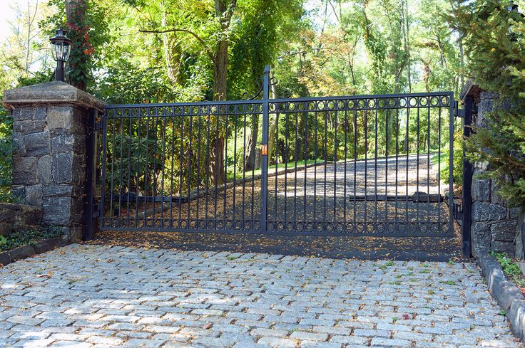 Wrought iron automated driveway gate. Circle details and streamlined design. By Tri State Gate in Westchester County, New York.