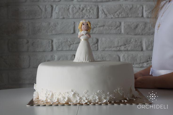 Orchideli – biały tort komunijny z figurką dziewczynki i delikatnymi kwiatuszkami, white first communion cake with fondant girl figurine on top and flowers.