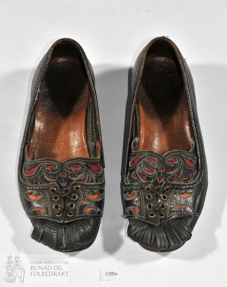 Håndsydde sko til kvinne med utklypte applikasjonar, snøring og duskar. Mørkebrunt lær. Trenagla sålar.