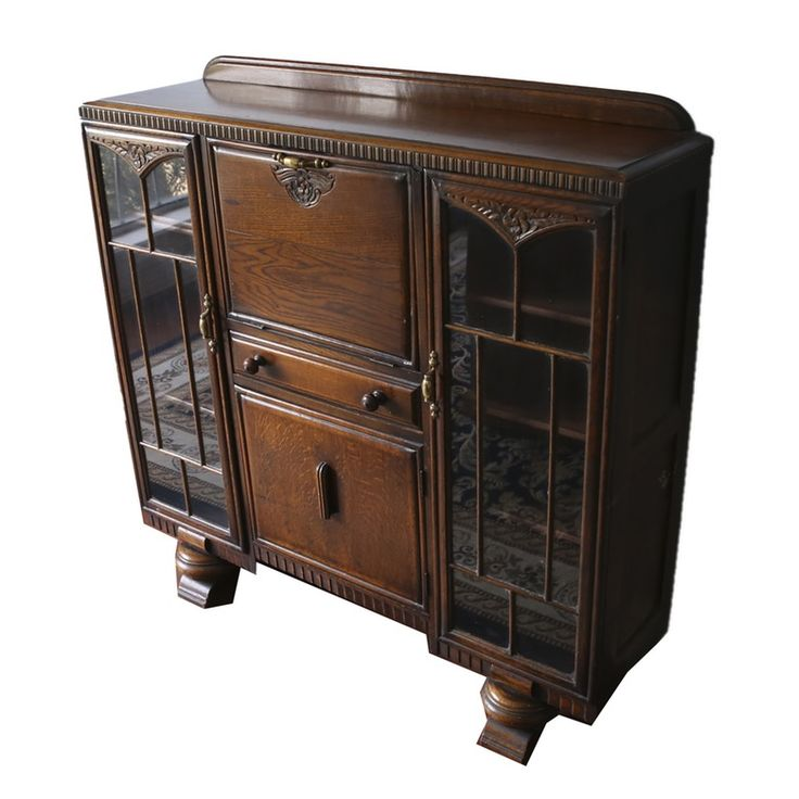An antique secretary hutch. This beautifully crafted furniture piece features two cabinet sections to the sides with paned glass doors. The center of hutch features a small drop down desktop, a single drawer, and another cabinet space. The piece is accented with dentil trim along the top and bottom edge and carved floral designs. It is stained a rich mahogany color.