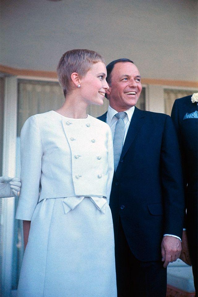 MIA FARROW/ミア・ファロー:ノーカラーの七分袖ジャケットと膝丈スカートを、ベリーショートでフレッシュに着こなし。式場は新郎所有のラスベガス「サンズホテル」だったそう!©amanaimages