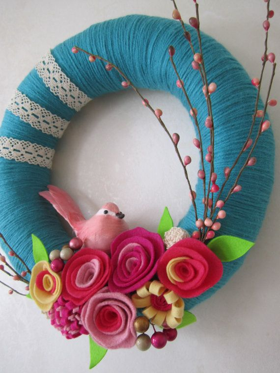 12 inch straw wreath wrapped in teal yarn, decorated with floral spray, lace buds and felt flowers. This is for purchase so no instructions, but great idea!
