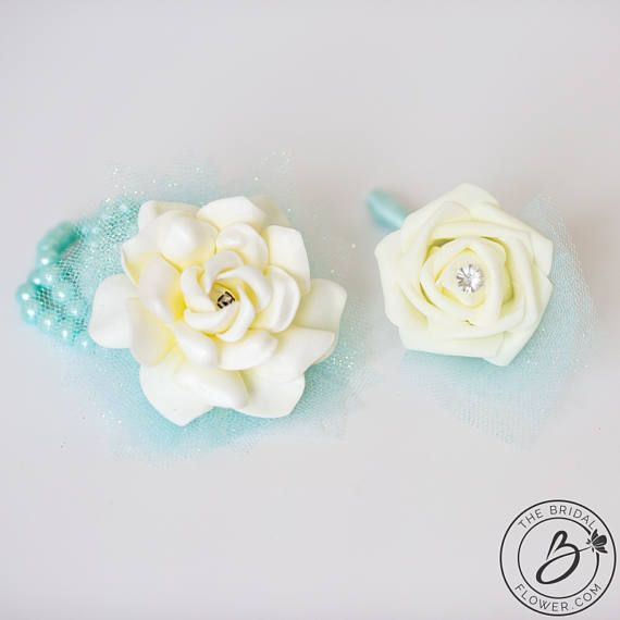 Beautiful corsage and boutonniere prom set perfect for your 2017 prom - ready to ship!  - Corsage Made with ivory gardenia (artificial) and accented with beautiful glittery turquoise tulle. Simple but elegant! Settled on a turquoise pearl bracelet which is the perfect accessory for your prom! Dimensions: approx. 3 wide  - Boutonniere Made with ivory rosebud (artificial) and accented with matching tulle and wrapped in black satin ribbon. Clear pin in the middle of the rose for a perfect…