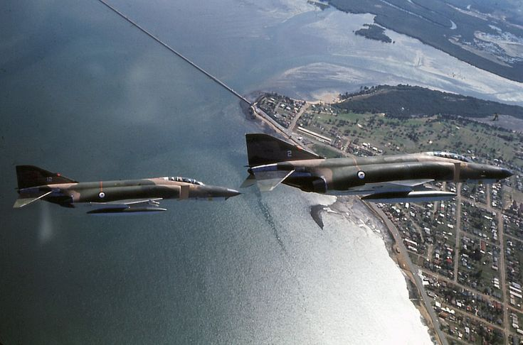 Air-to-air photo of RAAF F4-E Phantom 69-7202 leading 69-7212 over Woody Point, Queensland, Australia.