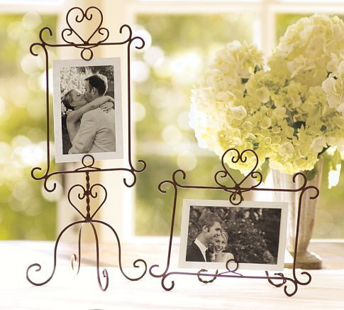 """pb 14-19. Suspend photos, love notes and mementos within these fanciful wire frames, hand shaped from wire with a rusted-bronze patina.        7.5"""" square, 15"""" high; holds a 4 x 6"""" photo      9"""" wide x 7.5"""" high x 3.5"""" deep; holds a 6.5 x 4"""" photo      Made of hand-twisted iron wire with an open area for floating a photo."""
